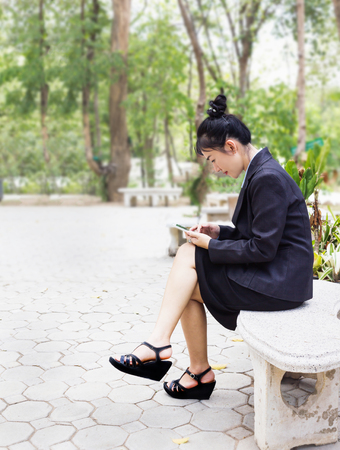 Single Asian business women sitting on branch surfing internet on smart phone or mobile in the park