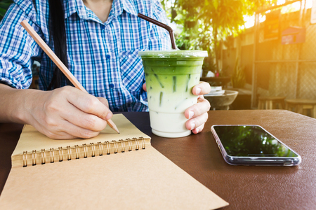 Hand with cool green tea and ice in plastic cup while writing on blank note book or diary in fresh nature garden home background Stock Photo