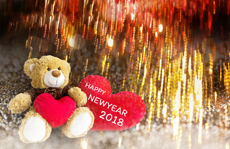 Lovely brown bear gift doll an red hearts on golden bokeh and firework abstract new year or Xmas celebration background with text two thousand eight teen Stock Photo