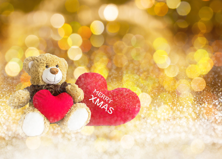 Lovely brown bear gift doll an red hearts on golden bokeh abstract new year or Xmas celebration background with text merry Xmas