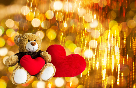 Lovely brown bear gift doll an red hearts on golden bokeh and firework abstract new year or Xmas celebration background Stock Photo