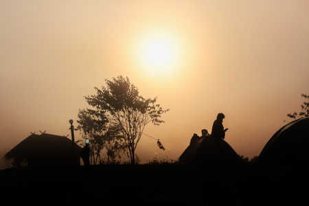 Silhouette dark man, hut and tree shadow in densely fog in winter morning with sunrise background on sky Standard-Bild