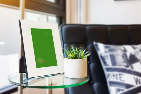 Blank picture white frame on table in living room with sofa background and small plant