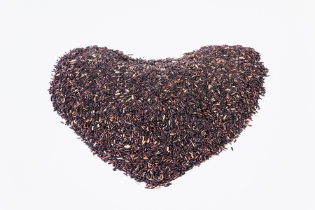 Organic natural healthy rice berry in heart shape on white background, purple rice