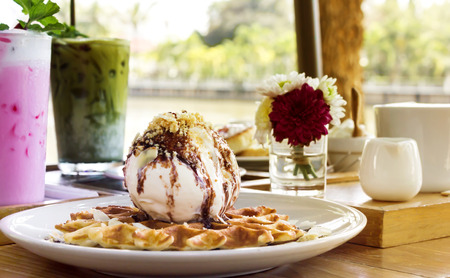 Big scoop vanilla icecream topping chocolate on waffle with drink or beverage background in garden beside the river
