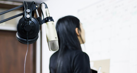 Microphone and earphone with blur background women looking to white board in studio working
