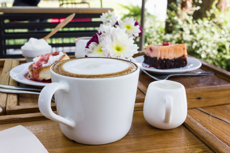 Cup of hot coffee on wooden table  with background of cake and flower