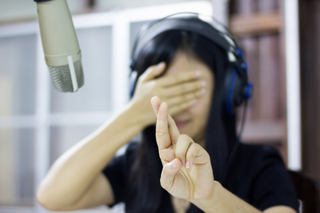 Microphone in studio with blurred Asian women do finger symbol of lie Standard-Bild