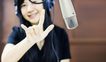 Microphone in studio with blurred Asian women smiling with finger symbol of love Standard-Bild - 103214318