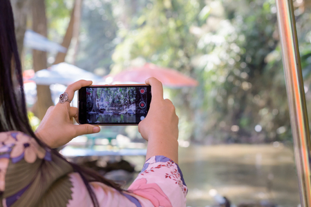 Hand shooting video clip of waterfall, lifestyle with smartphone camera in summer traveling