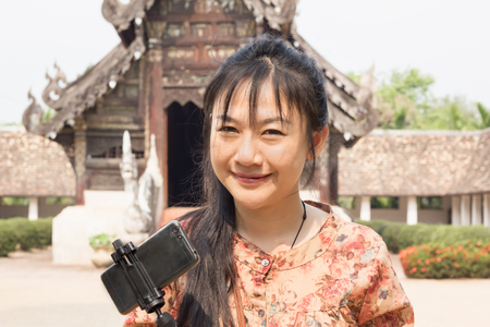 Smiling Asian long hair women with smartphone , portrait beautiful Asian lady with temple background Standard-Bild