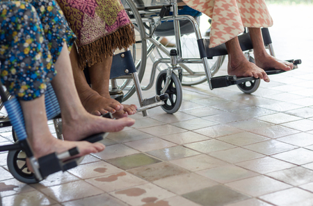 Close-up at feet of the group of wheelchair and elderly on wheelchair Standard-Bild