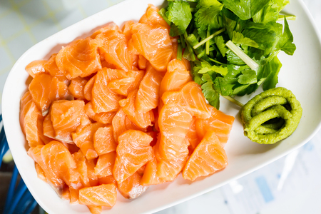 Top view salmon fish sliced in white dish with wasabi