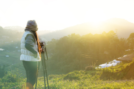 Back or rare view women shooting sunrise on mountain in green nature background, women wearing winter suit taking photo of sunrise in the morning Standard-Bild