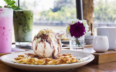 Chocolate and almond topping big scoop of icecream on waffle with garden summer view