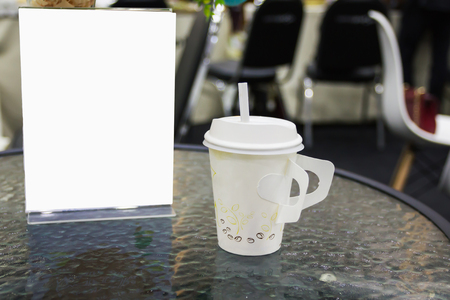Paper cup of cofee on table with blank or empty space sign or tent card in matching business event