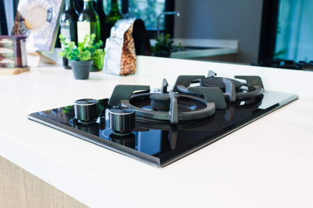 New modern clean built-in gas stove in kitchen, top view of gas stove at counter in home