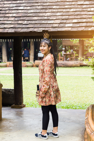 Long black hair smiling Asian women or lady in summer flower dress standing in folk village Standard-Bild