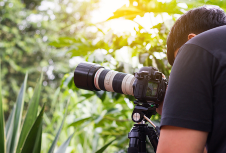 Big camera with zoom lens and a black hair men or photographer, working or hobby ,shooting nature