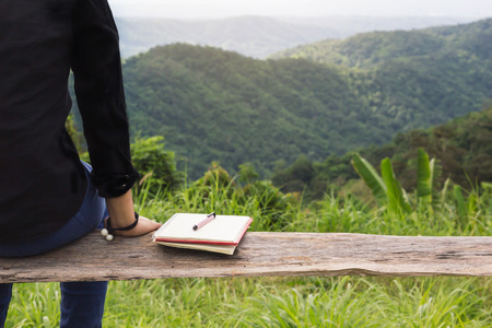 Back of rare view women sit on wood bench with black or empty diary or book with copy sapce and the background of mountain and forest, no inspiration or find inspiration concept Standard-Bild