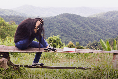 Long black hair Asian women sitting on wood bence with sad and dismal gesture with mountain and forest background and the blank diary or empty book infront of her Standard-Bild