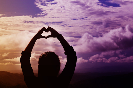 Back or rare view women do hand symbol of heart in fantasy dreamy violet and orange light wide sky with densely cloud and copy space in the concept of love and romantic Standard-Bild
