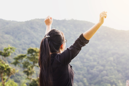 Asian women or girl raise arms open to sky with mountain and forest view, concept freedom in the fresh sunny morning