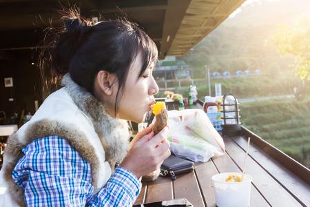 Asian girl eating sweet potato in warm sunlight