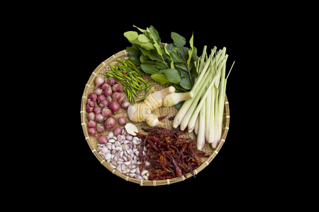 Isolate various Thai herbal ingredient for food, galangal, dried big red chili, small green fresh chilli, garlic, shallot, kaffir lime leaves and lemongrass on Thai style weaved wooden plate on black background