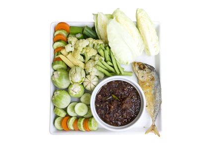 Isolated top view various boiled and fresh vegetable, lettuce, cucumber, carrot, young corn, cauliflower, eggplant with deep fried mackerel fish and chilli paste or chili dip in white plate
