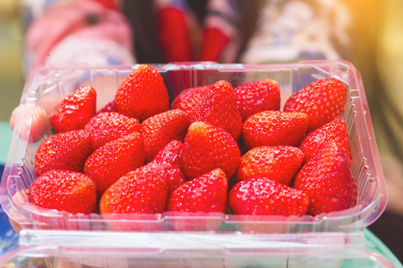 Group of strawberry in plastic box packaging with blur hand, summer mood
