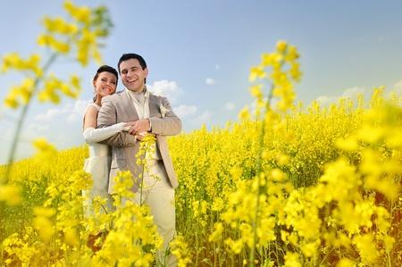 Newly-married couple in a rape field Stock Photo - 10795095