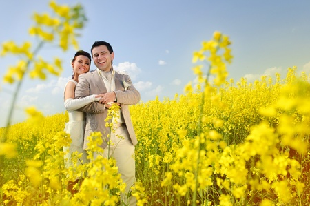 Newly-married couple in a rape field Stock Photo - 10795095