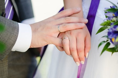 Newlyweds holding hands, their weddingbands showing Stock Photo - 10878694