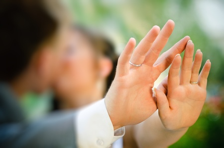 Groom and bride kissing and holding hand photo