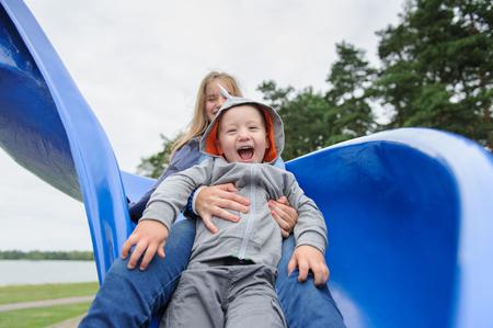 Smiling girl and boy having fun on childrens slide Zdjęcie Seryjne
