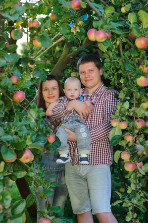 Happy parents with child in apple garden