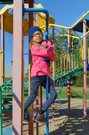 Little girl on outdoor playground equipment