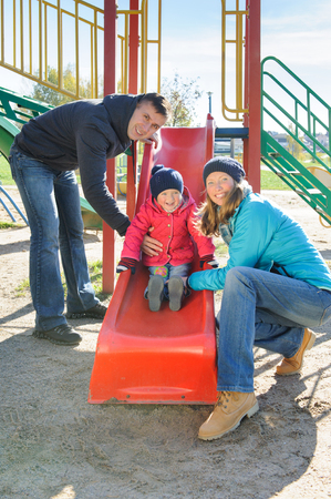 Parents with daughter playing at childrens slide