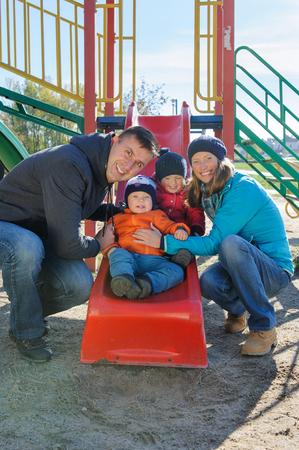 Happy smiling young family of four at childrens playground in park