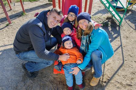 Happy smiling young family of five at childrens playground in park