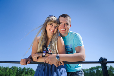 Young happy beautiful couple on blue sky background