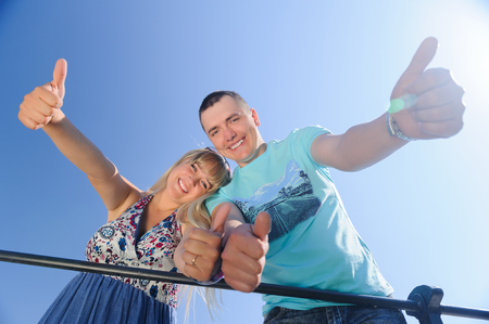 Smiling young happy couple showing thumbs up Zdjęcie Seryjne