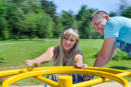 Young couple having fun on carousel on playground Zdjęcie Seryjne