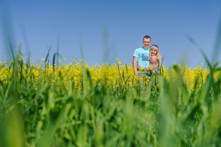 Portrait of young beautiful couple in rape field