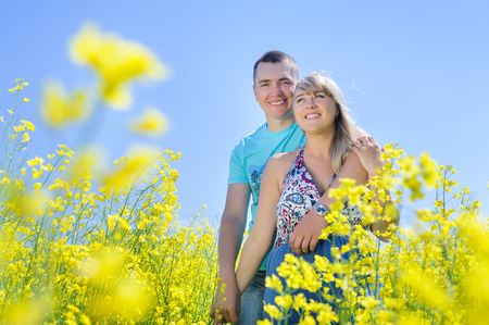 Happy couple in yellow rape field.