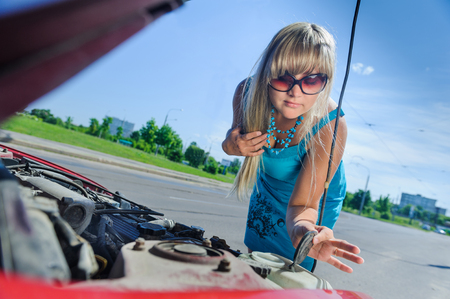 Beautiful blonde girl looking under the hood of the car