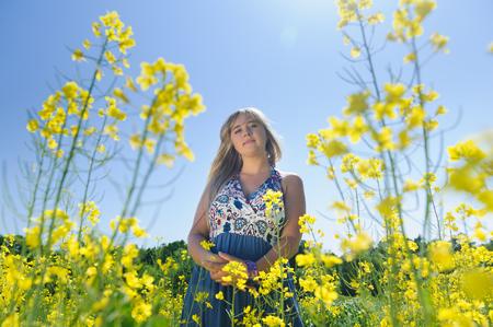 Cute woman in a yellow flowers field