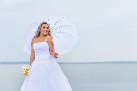 Beautiful bride in white dress with an umbrella Zdjęcie Seryjne