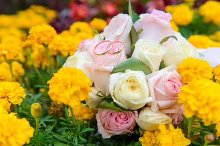 Wedding rings on wedding bouquet in flowers